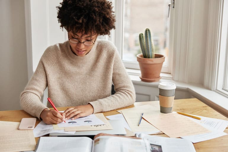Woman at her desk working on PMP exam