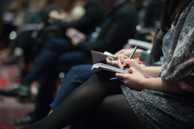 Close up people taking notes at a conference