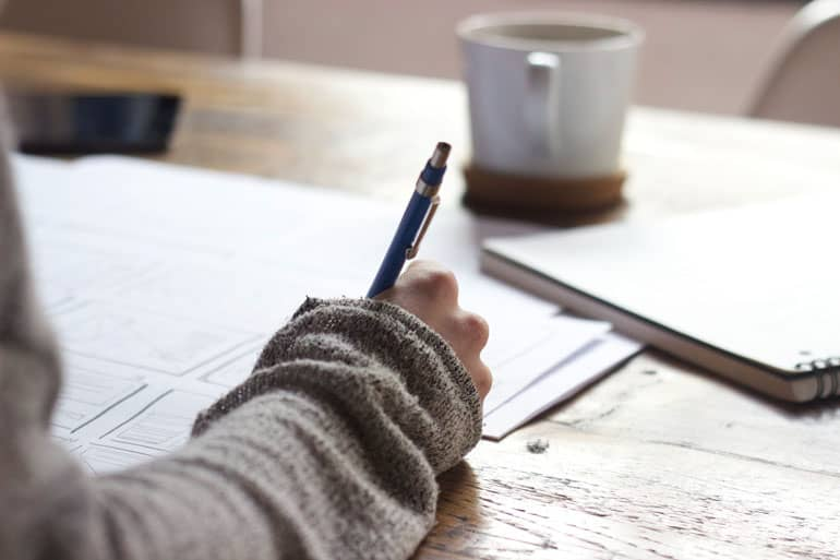 Close up of a person's hand writing for work