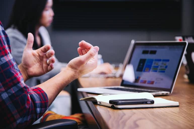Close of a team member using hands to explain PMP exam benefits