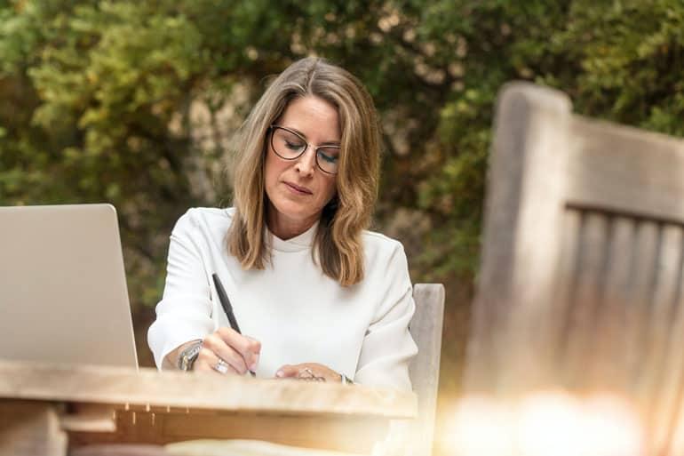 Woman writing a project communication plan