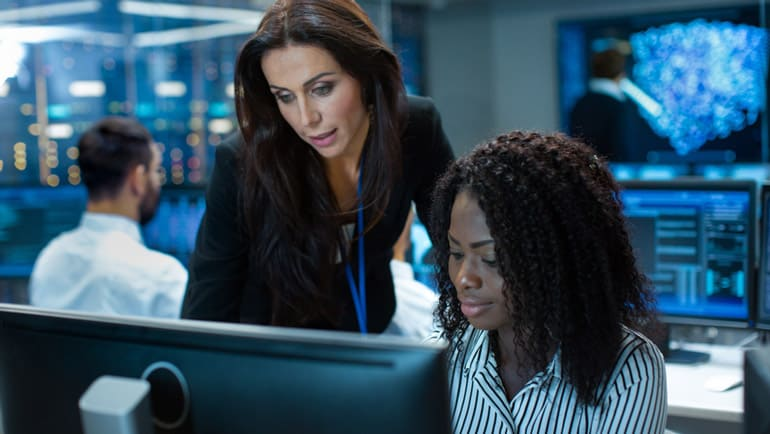 Two female colleagues discuss the project management trend of artificial intelligence