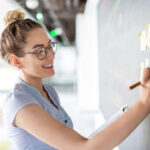 Woman at white board working on agile implementation